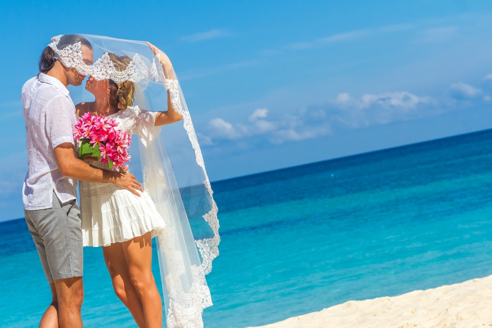 bride and groom, young loving couple, on their wedding day, outdoor beach wedding on tropical beach and sea background